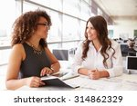 Two Women Working Together At...