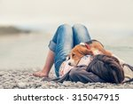 Stock photo little beagle puppy lying on his owner chest at the sea side 315047915