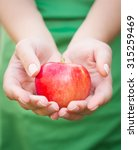 Red Apple In Hand On Green...
