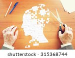 Stock photo man gathers a human head as puzzles on the wooden desk 315368744