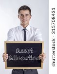 Small photo of Asset Allocation - Young businessman holding chalkboard with text