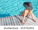 Woman Sitting On The Deck By...
