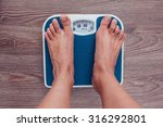 girl is measuring her weight on ... | Shutterstock . vector #316292801