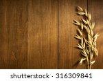 ears of oat on wooden background | Shutterstock . vector #316309841