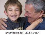 Boy giving his grandfather a huge hug - stock photo
