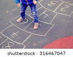 Kid Playing Hopscotch On...