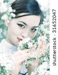 Young woman with cherry flowers portrait. Bright white and cyan tint. - stock photo