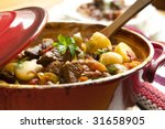 Traditional goulash or beef stew, in red crock pot, ready to serve.  Shallow DOF. - stock photo