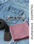 Small photo of Reading glasses, belt and hankie on denim shirt