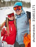 Small photo of Couple of happy snowboarders in winter activewear looking at camera on resort