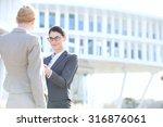 businesswomen shaking hands... | Shutterstock . vector #316876061