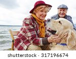 Stock photo retired woman cuddling cute pet with her husband on background 317196674