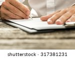 Small photo of Low angle view of male hand signing contract or subscription form with a pen on a rustic wooden desk.