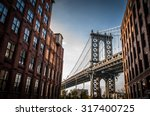 Stock photo manhattan bridge seen from a narrow alley enclosed by two brick buildings on a sunny day in summer 317400725
