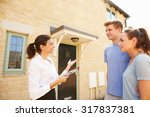 Small photo of Young couple viewing a house with female real estate agent