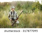 Small photo of woman hunter with shotgun looking through binoculars in forest