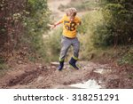 boy in gumboots jumps into the... | Shutterstock . vector #318251291
