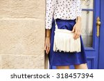 Small photo of Slim tanned girl in clothes in a marine style. Marine style of dress. White bag with fringe. Indigo blue. Saturated blue. Street fashion. Fashion model. Fashion street look. Items of clothing.