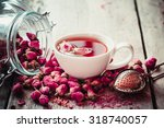 Stock photo rose buds tea tea cup strainer and glass jar with rosebuds selective focus 318740057