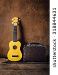 Small photo of still life of yellow ukulele and bag leather with brown leather background