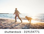 Stock photo young caucasian male playing with labrador on beach during sunrise or sunset man and dog having 319154771
