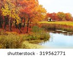 Stock photo autumn rural landscape autumn oak trees near the pond and lonely small house in foggy cloudy 319562771