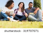 students sitting on the grass... | Shutterstock . vector #319707071