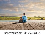 a boy and his dog sitting on a... | Shutterstock . vector #319765334