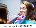 dentist curing a woman patient... | Shutterstock . vector #319784171