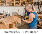 Young adult female woodworker sawing wood plank with reciprocating electric saw - stock photo