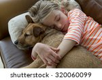 Stock photo young girl cuddling her pet dog on a sofa at home 320060099