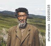 Small photo of Portrait Mongolian Man Field Senior Tranquil Solitude Concept