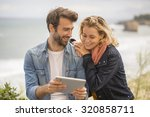 young couple using a digital... | Shutterstock . vector #320858711