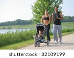 Young Couple Running Outdoor with Little Boy in Stroller Under Morning Sun Light - stock photo