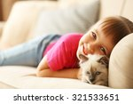 Stock photo little cute girl with kitten on sofa at home 321533651