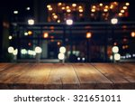 Stock photo image of wooden table in front of abstract blurred background of resturant lights 321651011