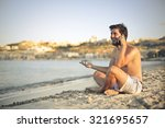 happy man sitting on the sand... | Shutterstock . vector #321695657