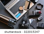 desktop with photography equipment, camera, tripod,flash  and computer - stock photo