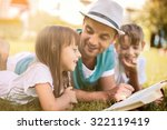 father reading a book to his... | Shutterstock . vector #322119419