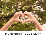 close up focus woman hands gesture make heart on blurred natural tree forest background at outdoor park  for good living happy life concept. - stock photo