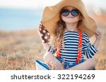 Stock photo pretty little girl in a striped dress and hat relaxing on the beach near sea summer vacation 322194269
