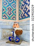 Small photo of The dall of the smiling Uzbek old man in the courtyard of Tilya Kori Madrasah, Samarkand, Uzbekistan.