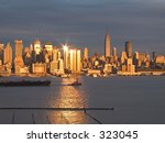 A tugboat pulls a barge along the Hudson River as the sunset reflects off the New York City skyline. - stock photo