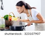 woman standing by the stove in... | Shutterstock . vector #323107907