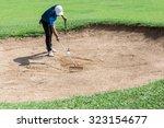 yong asia golfer raking bunker...
