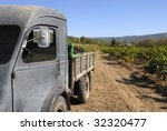 Old French truck with grapes during the harvest.At the background the vineyard. - stock photo
