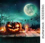 Stock photo halloween pumpkin on wooden plank with candles in a spooky night 323233361