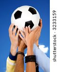 hands holding a football with a blue sky in the background - stock photo