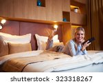 Stock photo young business woman relaxing in hotel room and looking tv 323318267