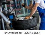 engineer  balancing  car wheel on balancer in workshop - stock photo